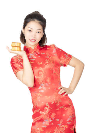 Photo pour Beautiful Chinese woman wearing a Cheongsam or Chipao holding a Moon Cake the traditional food of the Chinese holiday of Mid Autumn Festival isolated on a white background - image libre de droit