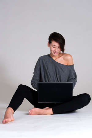 Studio shot of a multi raced yopung woman with her laptop on the floor