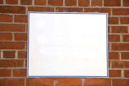 A blank white sign board against a brick wall ready for your text