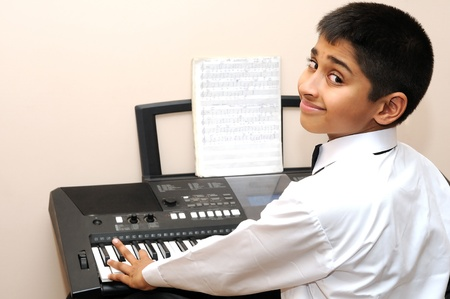 An handsome Indian boy learning music with an electric piano
