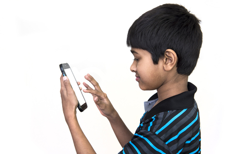 Photo for an handsome kid addicted to his mobie phone - Royalty Free Image