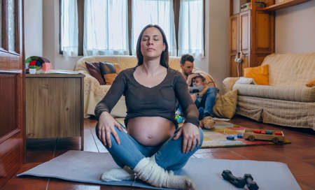 Pregnant woman exercising in the living room of her house