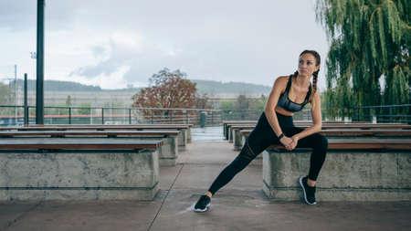 Foto de Young sportswoman posing sitting on a bench outdoors - Imagen libre de derechos