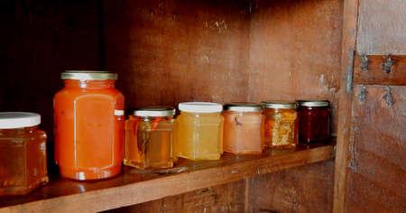 pots of confitures plusieurs piments parfums et de la passion fruit dans un meuble rustique en bois