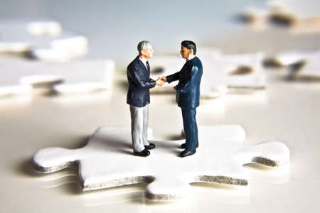 Photo for Businessman figurines shaking hands while standing on a puzzle piece - Royalty Free Image