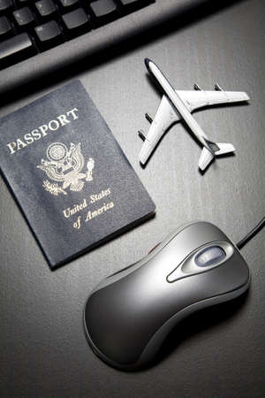 Metallic computer mouse, toy airplane and passport on a black wood tabletop