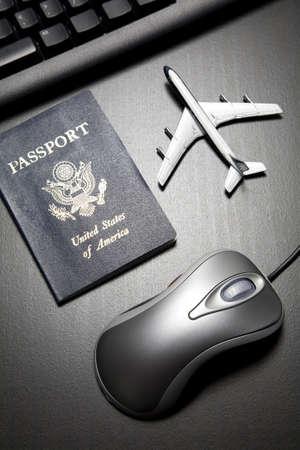 Foto de Metallic computer mouse, toy airplane and passport on a black wood tabletop - Imagen libre de derechos