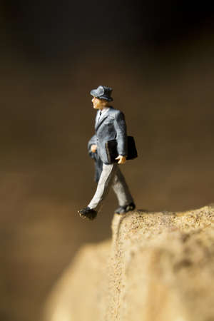 Businessman figurine posed to look like it is walking off a cliff
