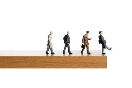 Business figurines walking off a ledge