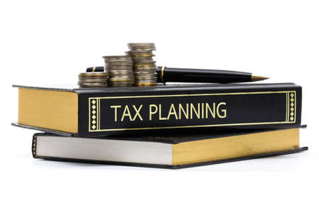 Tax planning book with coins and pen isolated on white