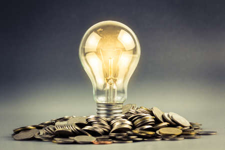 Photo for Light bulb and pile of coins - Royalty Free Image