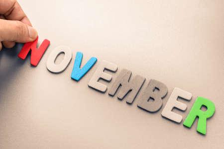 Hand arrange wood letters as November word