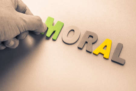 Hand arrange wood letters as Moral word