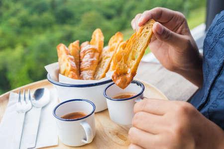 Closeup woman's hand dip croissant into sweet milk tea to eat
