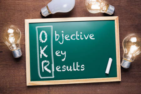 Photo pour OKR or Objective Key Results acronym text on chalkboard with many glowing light bulbs - image libre de droit