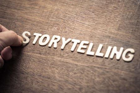 Photo pour STORYTELLING, closeup hand place a wood letter into the word for storytelling concept - image libre de droit