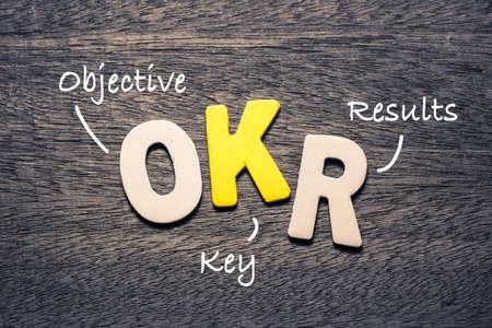 Photo pour OKR wooden alphabets on wood background with text acronym (Objective Key Results) - image libre de droit