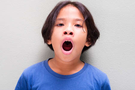 Photo for Nine years old Thai girl in blue t-shirt get tired and yawning - Royalty Free Image