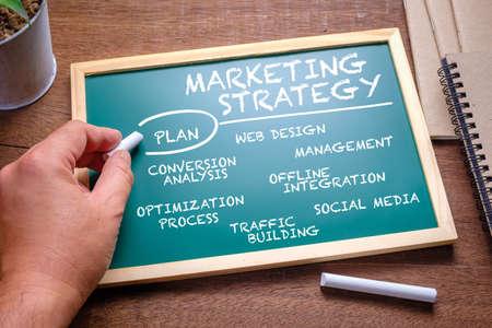 Photo pour Hand writing a digital marketing strategy concept on chalkboard - image libre de droit
