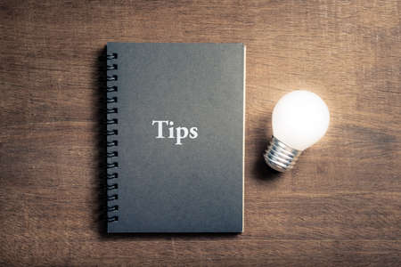 Photo pour Black notebook with text TIPS and glowing light bulb on wood background - image libre de droit