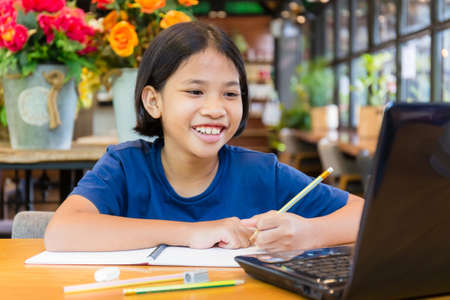 Photo pour Child girl is enjoy and smiling to the laptop, Thai child learn to educate herself by online content - image libre de droit