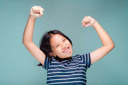 Photo for Ten years old girl clench her hand and lift the arms up with glad and satisfy to success, i can do it concept - Royalty Free Image