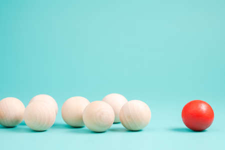 Foto de Different small red ball in the group of wooden balls on green background, leader or influencer with follower, branding and marketing concept - Imagen libre de derechos