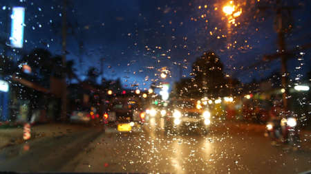 Photo for Thai songthaew bus with lit headlights traveling along night street during rain season. View through glass of car in drops. Romantic view of typical evening Asia. Public transport under stormy sky - Royalty Free Image