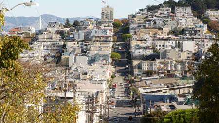Iconic hilly street and crossroads in San Francisco, Northern California, USA. Steep downhill road and pedestrian walkway. Downtown real estate, victorian townhouses abd other residential buildings.