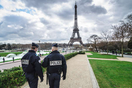 Paris, France - March 18, 2012: Patrols of two police officers in the Trocadero gardens and Eiffel Tower.