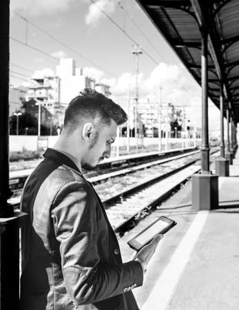 man reading a tablet or ebook in a train station while is waiting for public transport