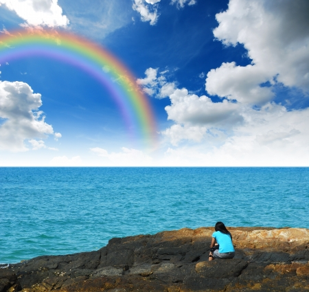 Alone woman on the beach wait for something hope for the future and lonely girl background design blue sky sea sand sun rainbow