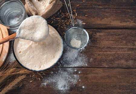 Photo for Stirring with a spoon of active starter culture. Ingredients for making bread. Tinted culinary background with copy space. - Royalty Free Image