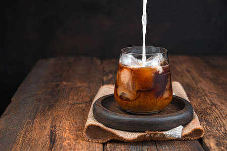 Photo pour Iced coffee with milk, cold drink in a glass on a dark background. Pouring milk into coffee. Copy space. - image libre de droit