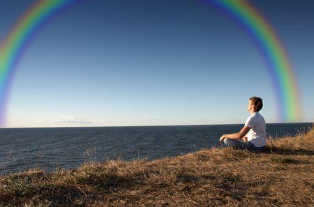 meditation at the seashore with big rainbow