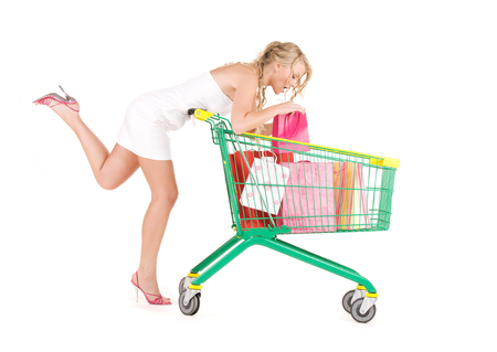 happy woman with shopping cart over white
