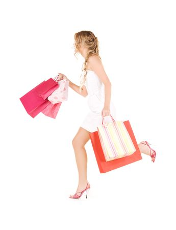 running woman with shopping bags over white