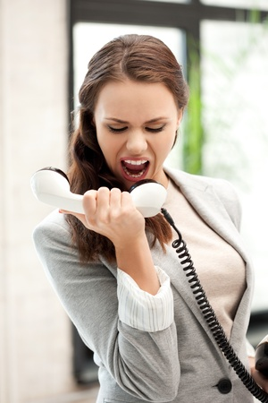 bright picture of angry businesswoman with phoneの写真素材