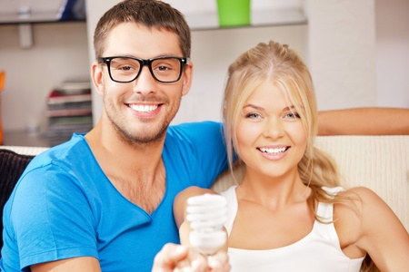 bright picture of happy couple holding energy saving bulb  focus on man