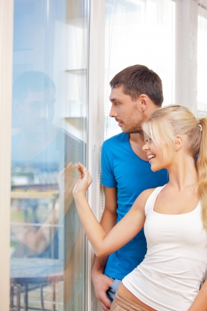 bright picture of happy couple at the window  focus on man の写真素材