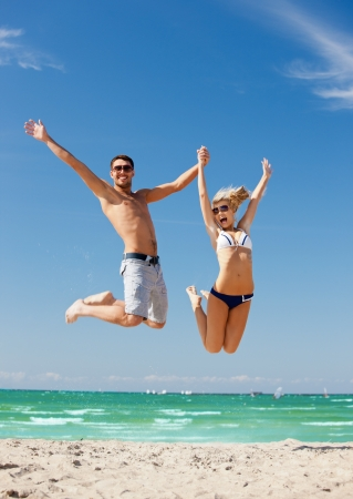 picture of happy couple jumping on the beach の写真素材