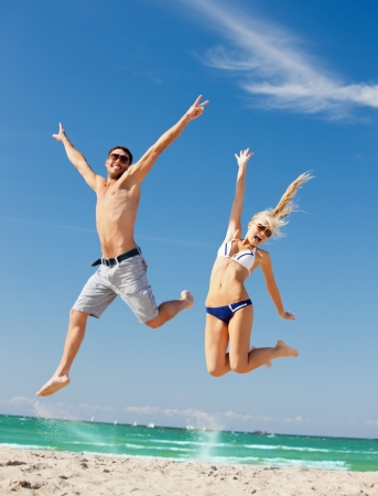 picture of happy couple jumping on the beach  focus on woman の写真素材