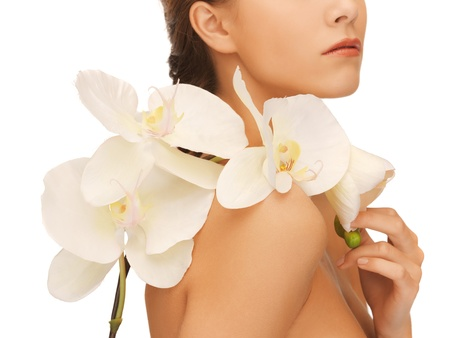 closeup picture of woman s shoulder and hands holding orchid flowerの写真素材