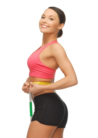 picture of sporty woman measuring her waist