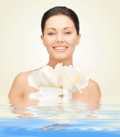 picture of lovely woman with orchid flower in waterの写真素材
