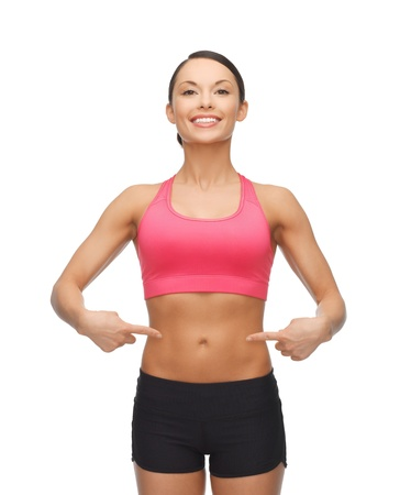 picture of beautiful sporty woman pointing at her six pack
