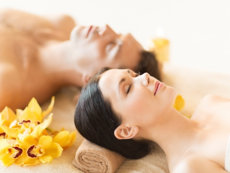 picture of couple in spa salon lying on the massage desksの写真素材