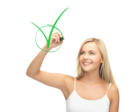 smiling woman in white shirt drawing green checkmark