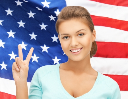 woman showing victory or peace sign over american flag