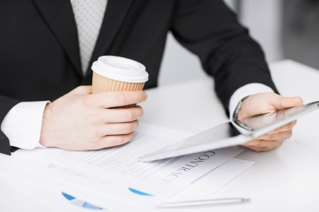 close up of man with tablet pc and cup of coffee